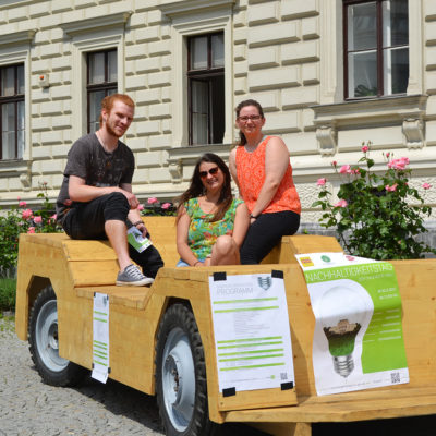 Aircampus Graz Studenten sitzen auf Holzauto