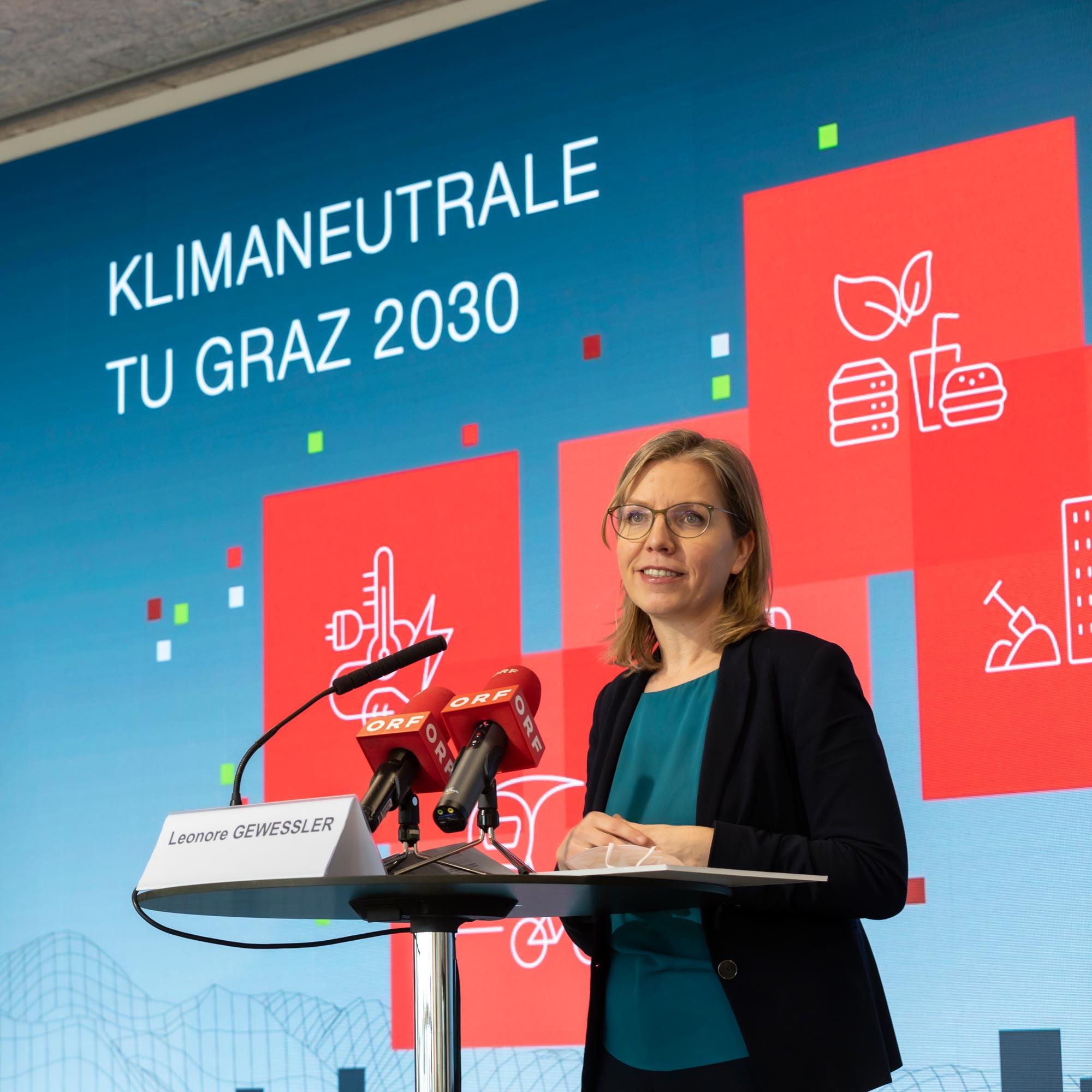 Österreichs Umweltministerin am Podium mit TV-Mikrofonen